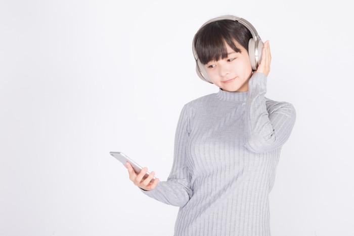 ヘッドフォンでスマホの音楽を聞いている女性